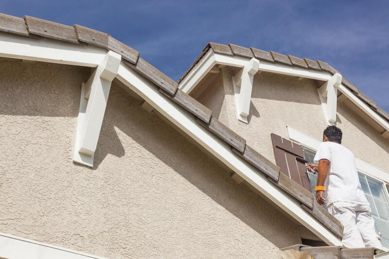 a man on the roof putting  exterior painting