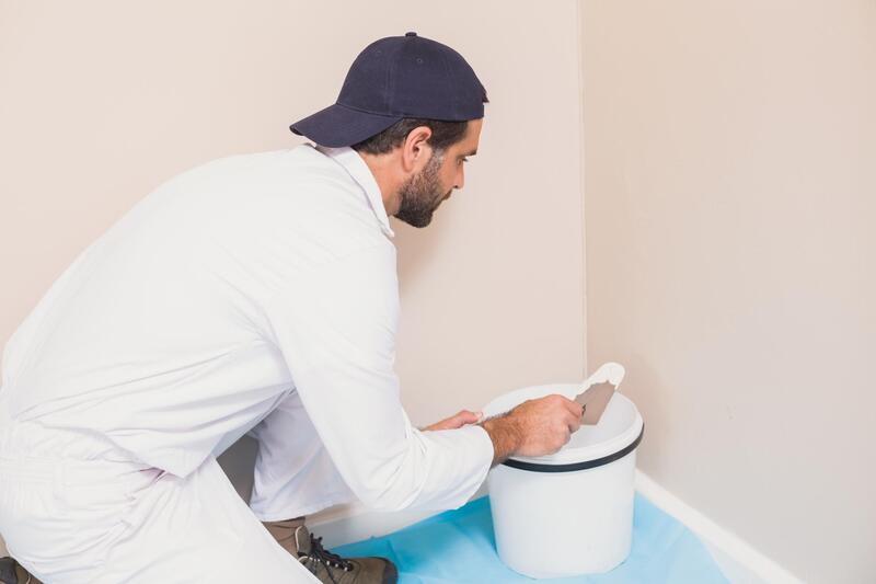 a painter paints the wall using brush